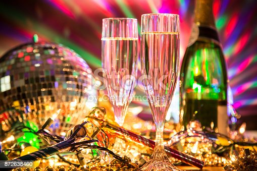 istock New Year's Eve holiday party with champagne, disco ball, decorations. 872638460