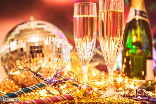 istock New Year's Eve holiday party with champagne, disco ball, decorations. 872638770