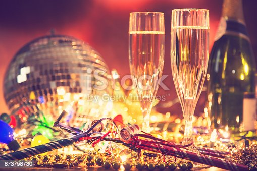 istock New Year's Eve holiday party with champagne, disco ball, decorations. 873758730