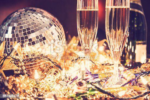 istock New Year's Eve holiday party with champagne, disco ball, decorations. 884992478