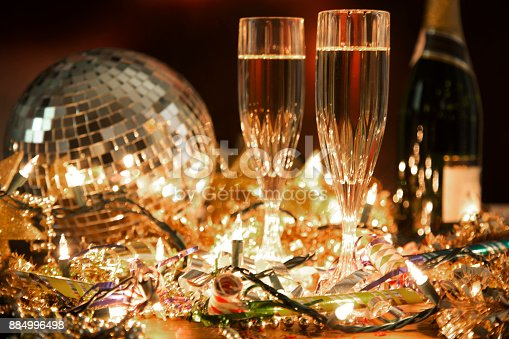 istock New Year's Eve holiday party with champagne, disco ball, decorations. 884996498