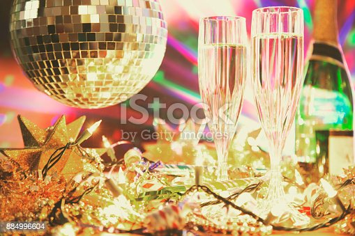 istock New Year's Eve holiday party with champagne, disco ball, decorations. 884996604