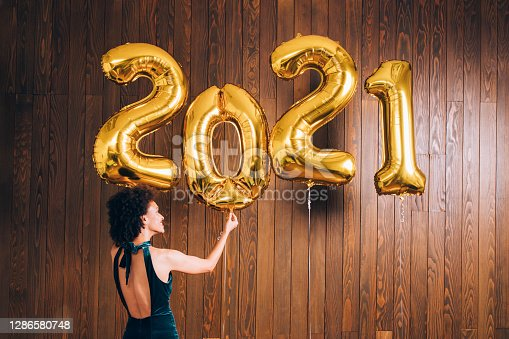 istock New Year's Eve Party: Happy African American Woman Decorating the Room with Huge '2021' Golden Balloons 1286580748