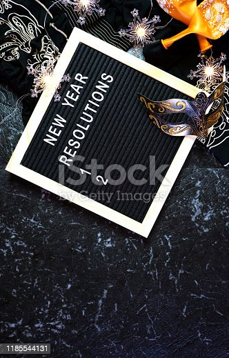 istock New Year's Eve resolutions letter board and black and gold party decorations. 1185544131