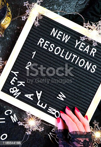 istock New Year's Eve resolutions letter board and black and gold party decorations. 1185544166