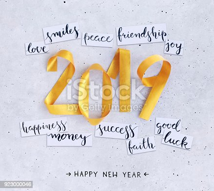 istock 2019 New Year's handwritten wishes on strips of white paper lying on a concrete background 923000046