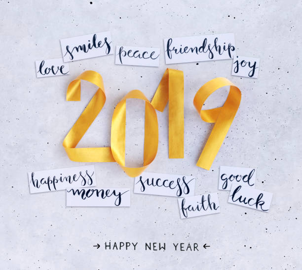 2019 New Year's handwritten wishes on strips of white paper lying on a concrete background stock photo