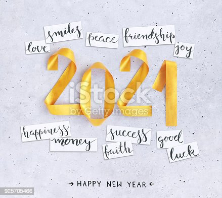 845307398istockphoto 2021 New Year's handwritten wishes with 3D handmade gold painted composition of numbers lying on a concrete background 925705466