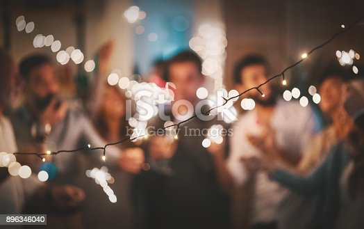 Closeup of group of  mixed age people having New year's party at home. They are having champagne, dancing and laughing. They are all out of focus and a string light in front of them is sharp