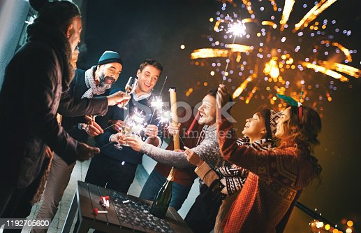 Closeup of group of mixed age people having Christmas and  New year's party on a balcony. They are dancing and sipping champagne as the fireworks pops in the background.