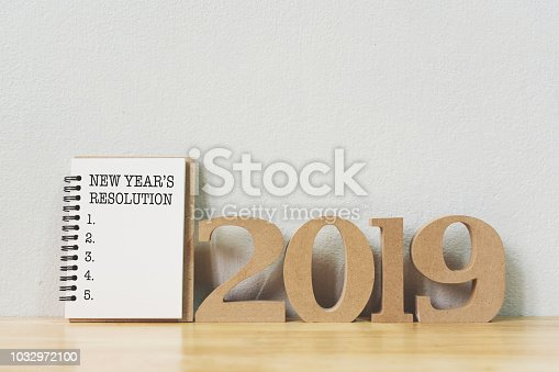 1076095678 istock photo New year's resolution on a notebook and wood number 2019 on wood table, Copy space 1032972100