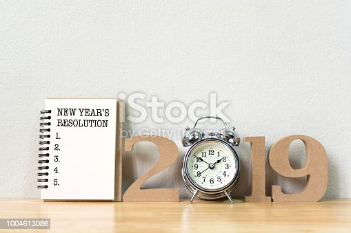 1076095678 istock photo New year's resolution on a notebook and wood number 2019 with clock on wood table and copy space 1004613086