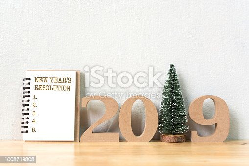 1057357020istockphoto New year's resolution on a notebook and wood number 2019 with christmas tree on wood table and copy space 1008719808