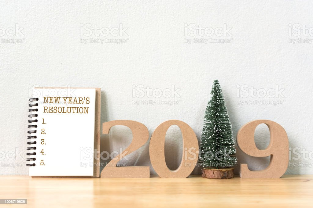 New year's resolution on a notebook and wood number 2019 with christmas tree on wood table and copy space stock photo