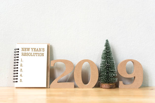 new year's resolution on a notebook and wood number 2019 with christmas tree on wood table and copy space - new year day stock photos and pictures
