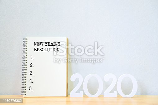 1076095678 istock photo New year's resolution on a notebook and wood number 2020 on wood table, Copy space 1160776302