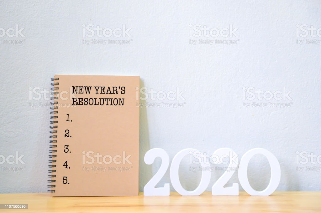 New year\'s resolution on a notebook and wood number 2020 on wood...