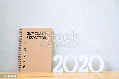 1076095678 istock photo New year's resolution on a notebook and wood number 2020 on wood table, Copy space 1167560595
