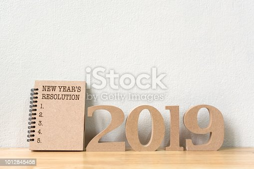 1076095678 istock photo New years resolution on a notebook brown colour  and wood number 2019 on wood table and copy space 1012845458