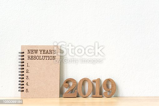 1076095678 istock photo New years resolution on a notebook brown colour  and wood number 2019 on wood table and copy space 1050099184