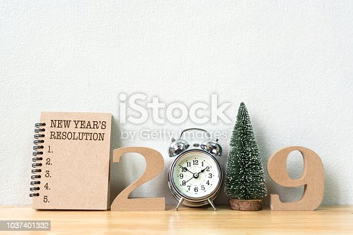1076095678 istock photo New year's resolution on notebook and wood number 2019 with clock and christmas tree on wood table and copy space 1037401332