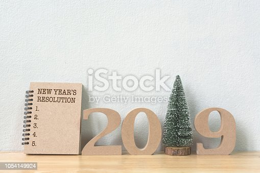 1076095678 istock photo New years resolution on notebook brown colour and wood number 2019 with christmas tree on wood table and copy space 1054149924