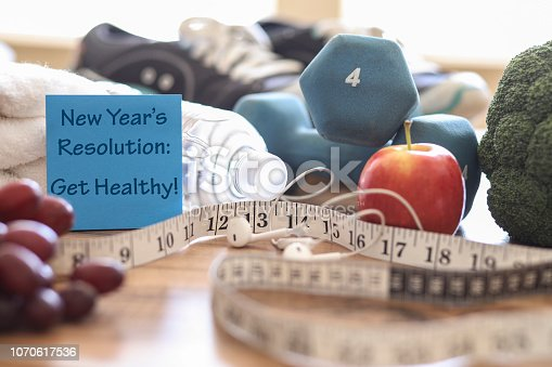 New year's resolution to get healthy in the coming year!  Group of objects includes:  note, fruit, tape measure,ear buds, athletic shoes, dumbbells, water bottle and towel.   Concept of an individual preparing items for an exercise.
