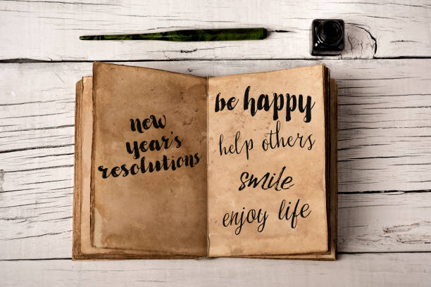 new years resolutions in a yellowish notebook stock photo