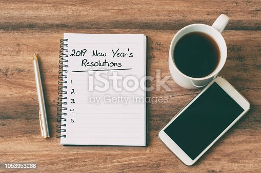New year Concept - 2019 New Year's Resolutions text on notepad. Smartphone, pen and cup of copy background.