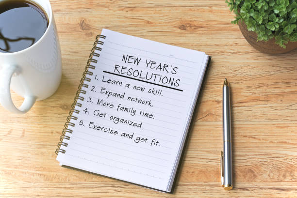 new year's resolutions written on notepad with pen, coffee and plant on top of wooden table. - new years day stock pictures, royalty-free photos & images