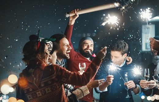 Closeup of group of mixed age people having New year's party at a building rooftop. They are having champagne, lighting up some fire sparklers and popping confetti.