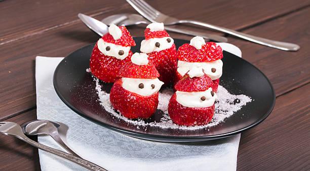 new year's snack from strawberry and cream - weihnachtsmannhüte aus erdbeeren stock-fotos und bilder