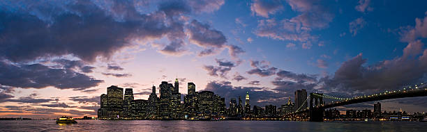 New York bright lights big sky sunset Deep blue and purple dramatic dusk cloudscape over the twinkling lights, iconic shore and landmarks of Lower Manhattan, from the islands and ferries of New York Harbor past the downtown skyscrapers to the soaring span of the Brooklyn Bridge. ProPhoto RGB profile for maximum color fidelity and gamut. south street seaport stock pictures, royalty-free photos & images