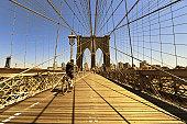 XXL - cyclist in front of manhattan brooklyn bridge in warm colors - wide angle - camera canon 5D mark II - unshapred RAW