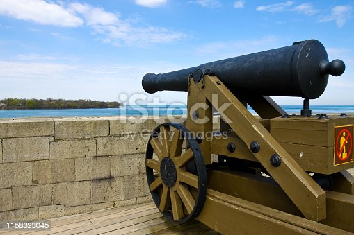 Taken this picture of the Niagara fort in Buffalo USA. In the picture is the french canon in foreground and the main building in background. There are tourists in background who are walking around.