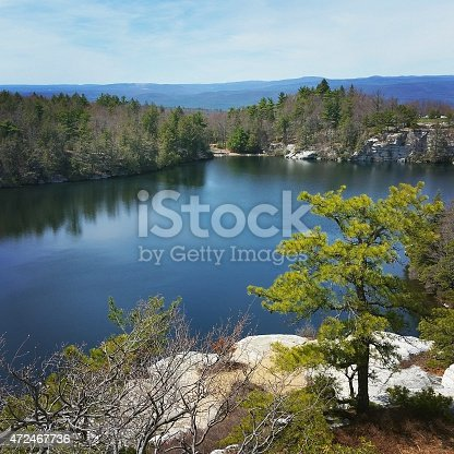 This is a square, color, royalty free mobilestock photograph shot with a Samsung Galaxy S5 on a spring day in New York State's Catskill Mountains. Pine trees line Lake Minnewaska and are reflected in the calm blue water surface. Mountains fill the background. A bright green pine tree stands out in the foreground of the natural scene.