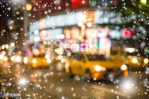 Defocused blur New York City  Manhattan street scene with yellow taxi cabs and snowflakes falling during winter snow storm