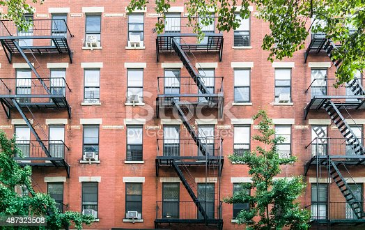 a typical example of New York City architecture with an apartment building with multiple fire escapes in red brick in a leafy street