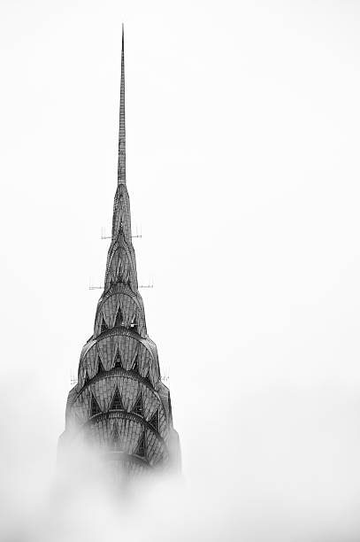 new york city chrysler building stands above steam clouds - chrysler building stock photos and pictures
