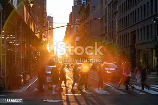 813211754 istock photo New York City - Crowds of people with the bright light of summer sunset shining between the buildings in the background 1183865027