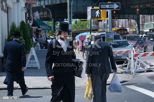 New York, United States - June 3, 2011: A young traditionally dressed hassidic man walks towards the camera, crossing the street in the opposite direction of an old man carrying groceries.
