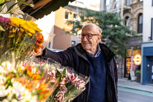 Senior caucasian man walking down the streets in New York city enjoying his free time.