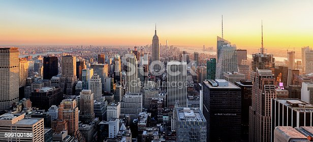 New York City. Manhattan downtown skyline with illuminated Empire State Building and skyscrapers at sunset.