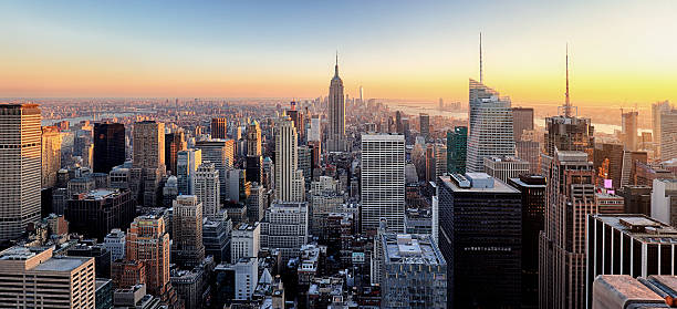New York City. Manhattan downtown skyline. New York City. Manhattan downtown skyline with illuminated Empire State Building and skyscrapers at sunset. new york state stock pictures, royalty-free photos & images