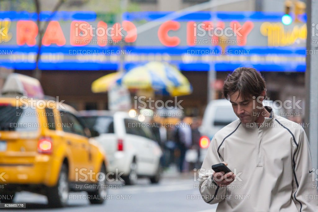 New York City -October 10: Mature Man at Times Square Standing With Cell Phone and featured  with NYC Taxi Behind Him, October 10,2013 stock photo