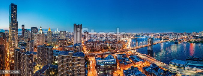 New York City Panoramic Aerial View at Dusk from Downtown looking towards midtown with views of Brooklyn Bridge, Manhattan bridge and the Empire State Building.