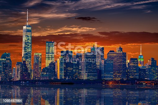 New York City Skyline, Illuminated Skyscrapers of the Lower Manhattan Reflected in the Water of New York Harbor and Vivid Sunset Sky are in the image. Canon EF 70-200 F/4L IS lens.