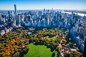 New York City skyline aerial view with Central Park in foreground and Manhattan cityscape skyline in background. Colorful autumn foliage in Central Park.