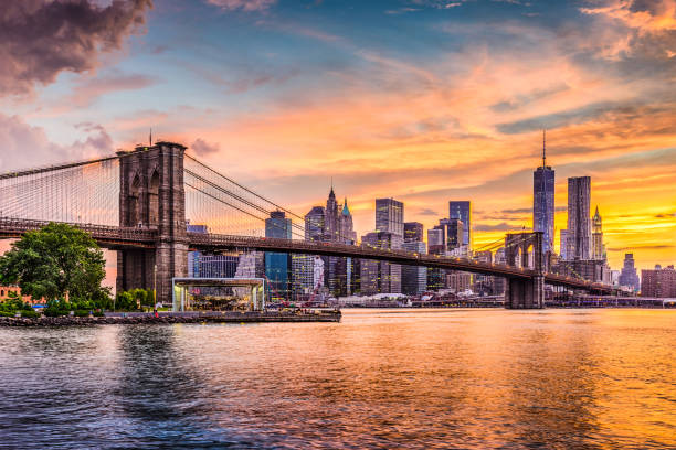 New York City Skyline New York City Skyline on the East River with Brooklyn Bridge at sunset. new york state stock pictures, royalty-free photos & images