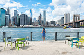New York city skyline waterfront lifestyle - American people walking enjoying view of Manhattan over the Hudson river from the Brooklyn side. NYC cityscape with a public boardwalk with tables.